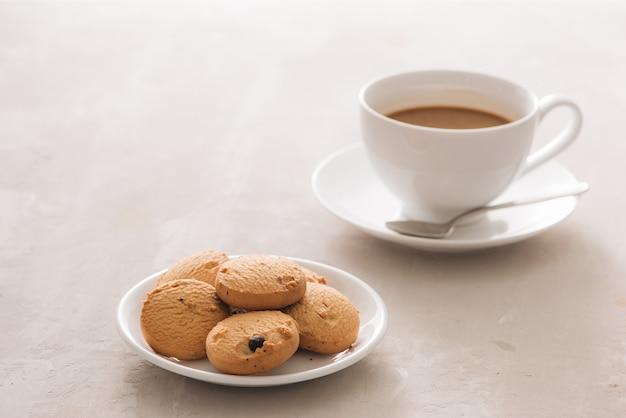 明るい背景にビスケット、スプーン、プレートとコーヒーの白い磁器カップ