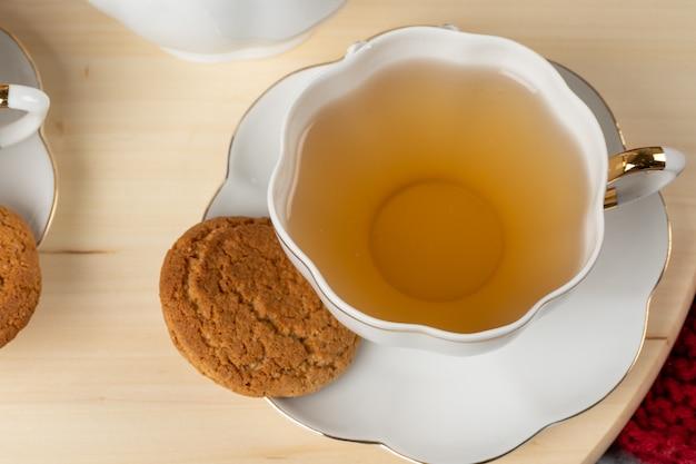 テーブルの上のお茶とオーツ麦クッキーの白い磁器カップ