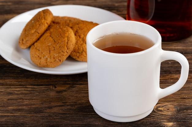 テーブルの上の紅茶とオート麦クッキーの白磁カップ