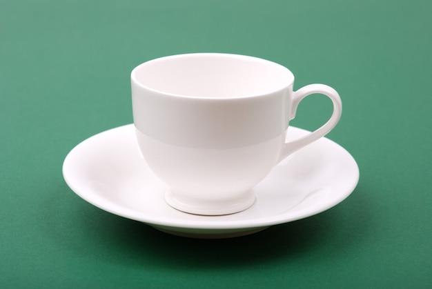 녹색 배경에 흰색 도자기 컵