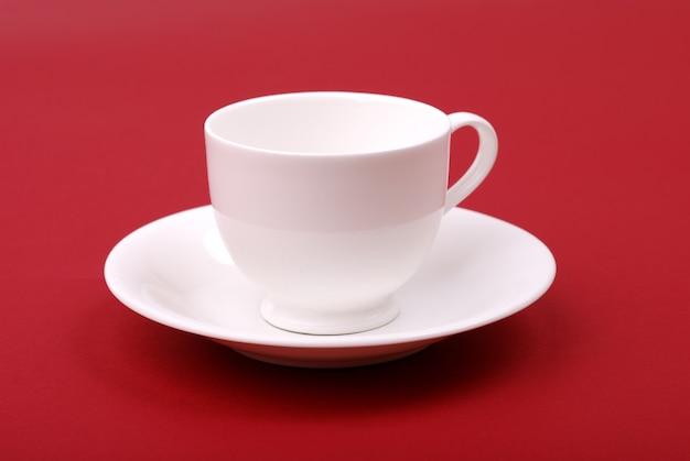 빨간색 배경에 흰색 도자기 컵