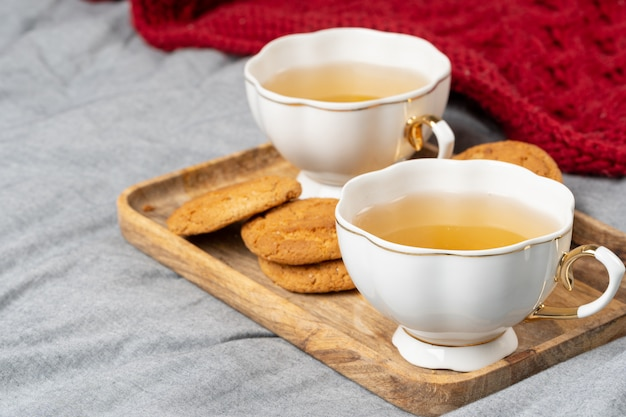 White porcelain cup of tea and oat cookies on a table