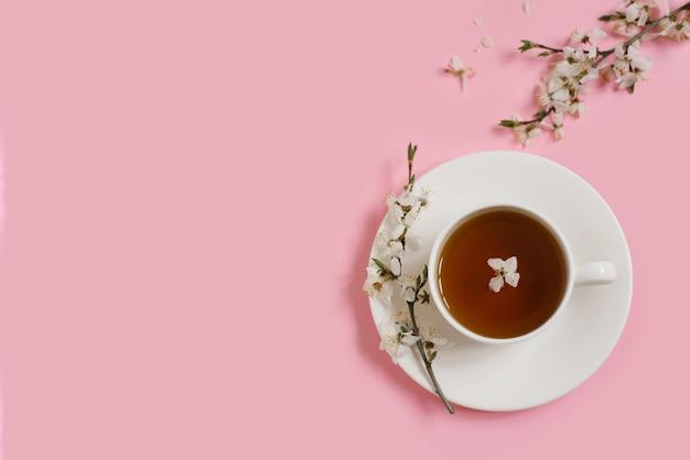 紅茶と白磁カップ。開花するリンゴの木の枝は、穏やかなピンクの背景にあります。春のコンセプト。スペースをコピーします。フラットレイ