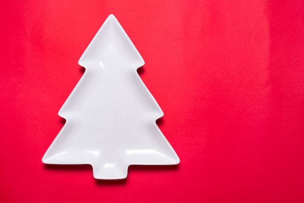 White porcelain plate christmas tree shaped on red background