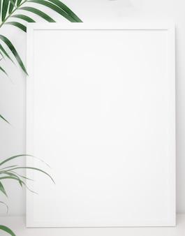 Белая рамка для плаката с зеленым пальмовым листом на белом фоне стены, копией пространства для вашего дизайна