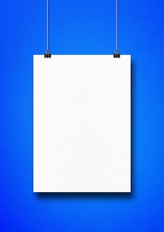 White poster hanging on a blue wall with clips.