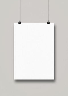 White poster hanging on a clean wall with clips.