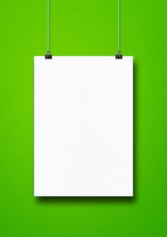 White poster hanging on a green wall with clips.