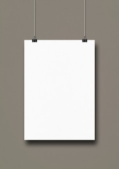 White poster hanging on a grey wall with clips.
