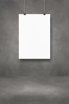 클립이 있는 어두운 콘크리트 벽에 흰색 포스터가 매달려 있습니다. 빈 모형 템플릿