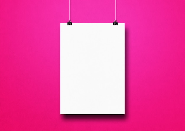 White poster hanging on a pink wall with clips.