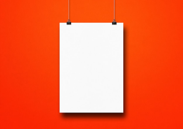 White poster hanging on a red wall with clips. blank template