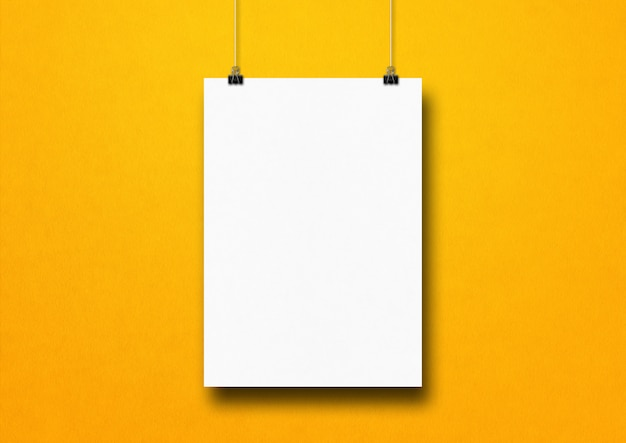 White poster hanging on a yellow wall with clips. blank mockup template