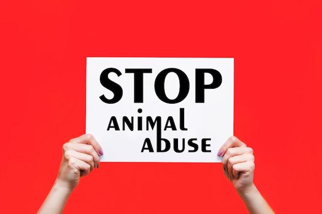 빨간색 배경에 격리된 여성의 손에 동물 학대를 중지하라는 슬로건이 있는 흰색 포스터