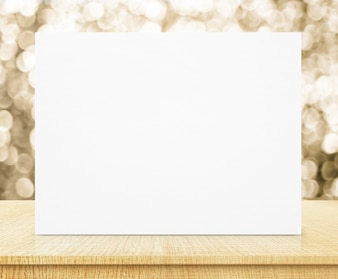 White poster with sparkling gold bokeh wall and wooden table