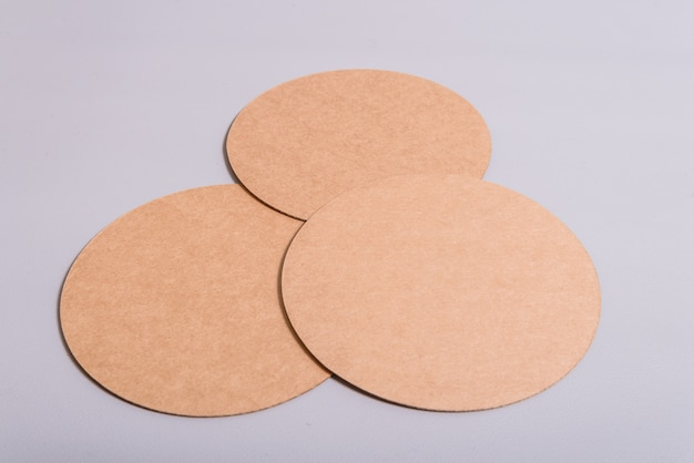 White potvelain tea of coffee cup on cound cardboard round coasters, cup pad, mat, holder