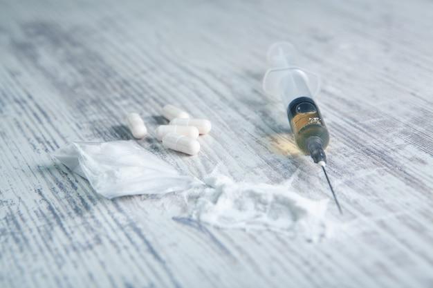 Белый порошок, капсулы и шприц на столе