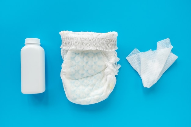 White powder, diaper, cream, napkin on a blue background, flatley, top view, copy space, mock up