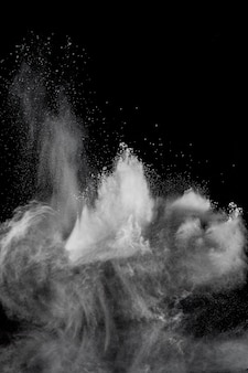 White powder explosion cloud against black background.white dust particles splash.