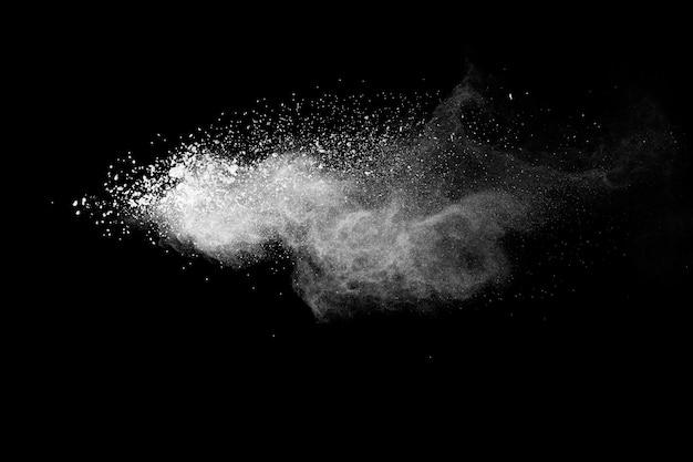 黒の背景に分離された白い粉の爆発。白い粉塵粒子が飛散。