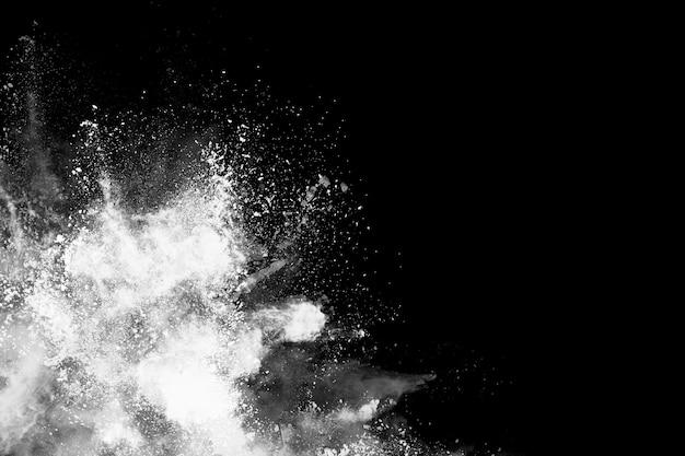 Взрыв белого порошка на черном фоне.