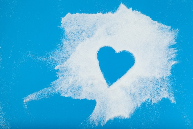 White powder is chaotically scattered on blue surface empty space in the form of heart