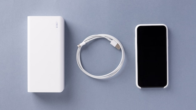 White power bank charger, usb cable and smartphone in a white case