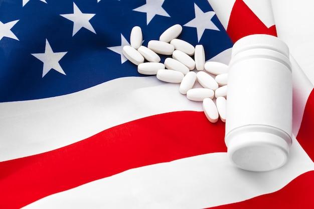 White prescription pills on united states flag