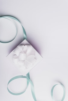 White present box with curled turquoise ribbon isolated on white background