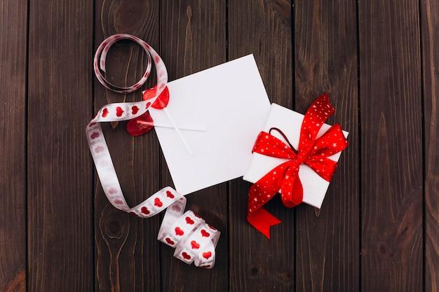 赤いリボンと白の現在のボックスは、木製のテーブル上の空のカードに立つ