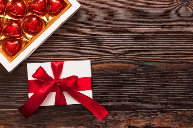 赤いリボンと暗い木製の背景に分離されたチョコレートの赤いハートのボックスと白いプレゼント。温かいフラットレイを祝う上面図。バレンタインデーとクリスマスのコンセプト。コピースペース。