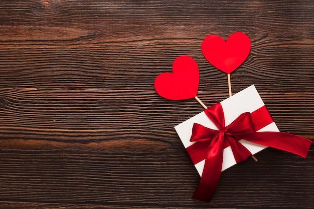 暗い木製の背景に分離された赤いリボンと紙のハートと白いプレゼント。温かいフラットレイを祝う上面図。バレンタインデーとクリスマスのコンセプト。コピースペース。