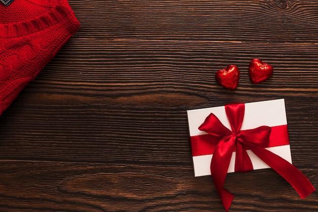 Белый подарок с красной лентой и двумя шоколадными красными сердцами, изолированными на темном деревянном фоне. вид сверху на празднование теплого flatlay. день святого валентина и рождество концепции. copyspace.