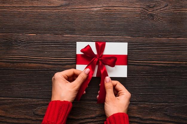 Белый подарок с красной лентой в руках женщины на темном деревянном фоне. валентина день концепция. copyspace.