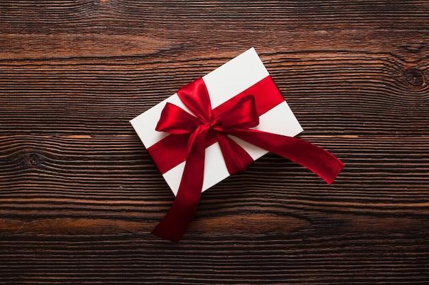 暗い木製の背景に分離された赤いリボンと白いプレゼント。温かいフラットレイを祝う上面図。バレンタインデーとクリスマスのコンセプト。