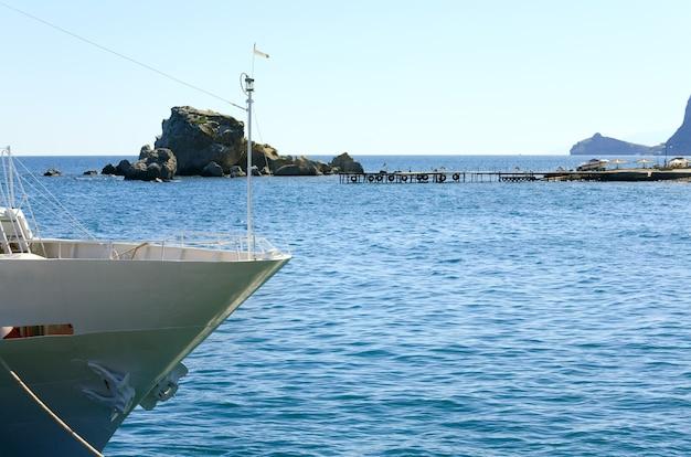 Белый нос экскурсионной туристической яхты и мерцание солнца на водной поверхности позади
