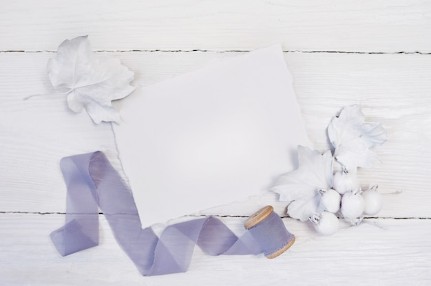 White pumpkin, berries and leaves and gray ribbon on a wooden background.