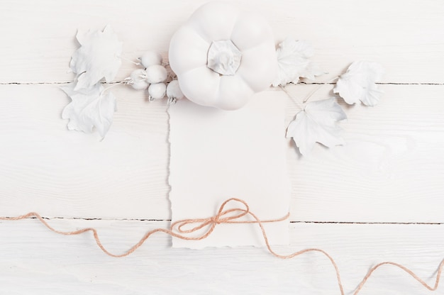 White pumpkin, berries and leaves and white sheet of paper and linen rope