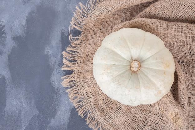 黄麻布で青い表面に白いカボチャ。