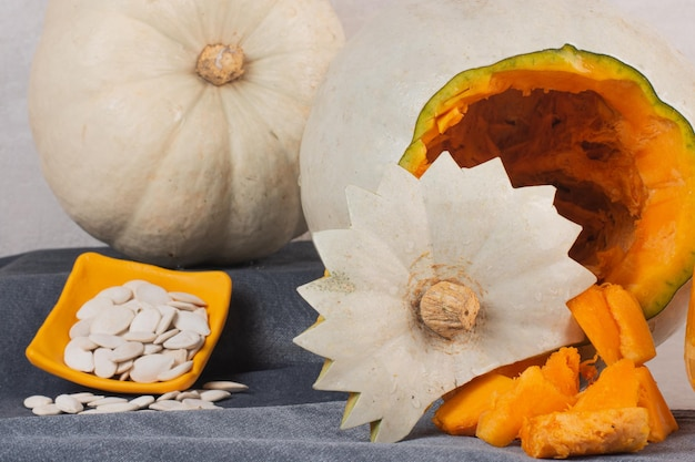 Zucca bianca e semi di zucca sul tavolo bianco.