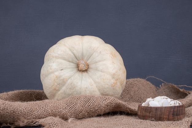 Zucca bianca e semi sulla superficie blu con tela.