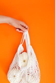 White pumpkins in mesh shopping bag on orange background