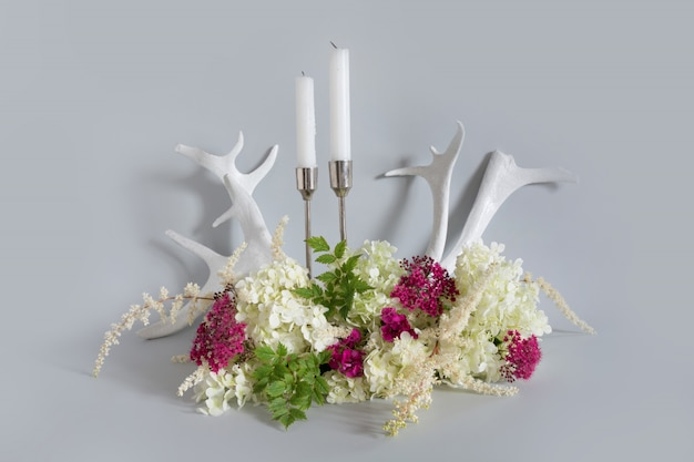 White and purple wildflowers, candle and reindeer antlers on pastel grey. nature composition.