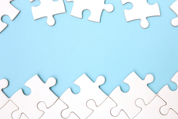 White puzzle frame on pastel blue background with copy space