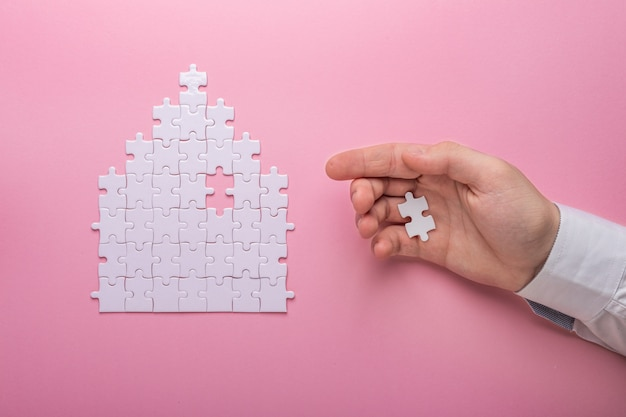 White puzzle. house shape puzzle. the concept of rent, mortgage. hand holding piece of white puzzle.
