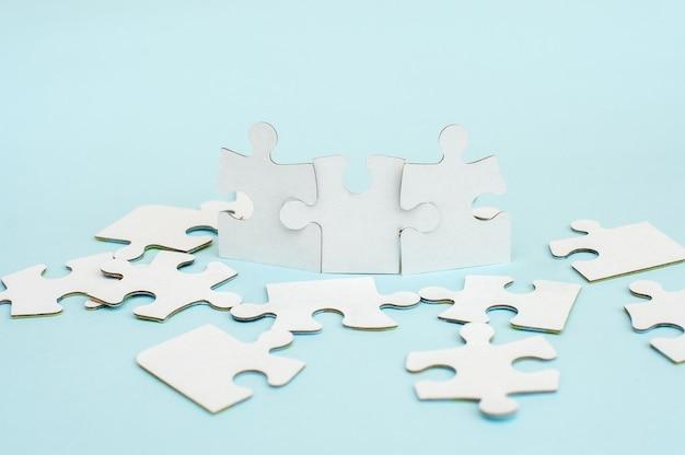 Белая головоломка на синем фоне. бизнес-концепция