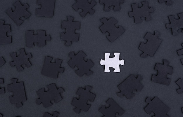 White puzzle piece on black with other black pieces.