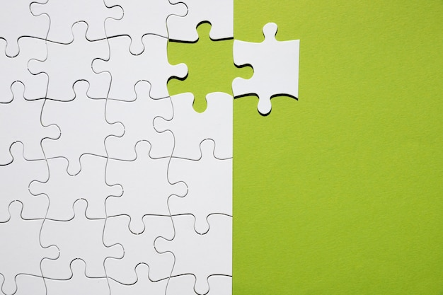 White puzzle piece separate with white puzzle grid on green backdrop
