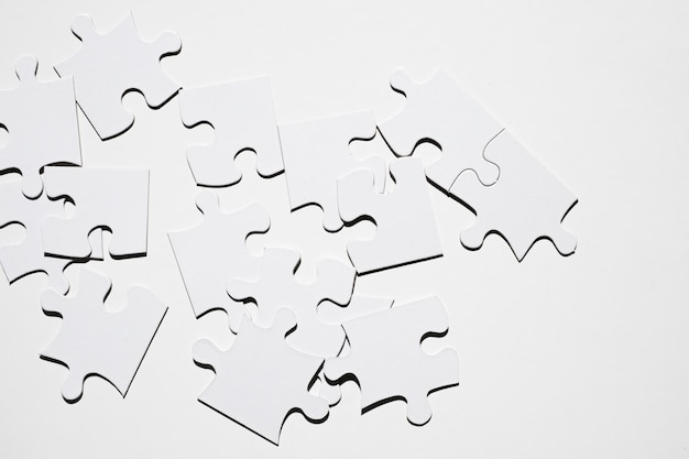 白い面に分離された白いパズルのピース