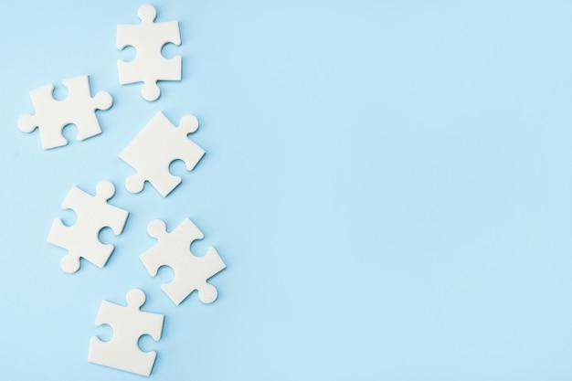 Белые кусочки головоломки на синей стене с копией пространства
